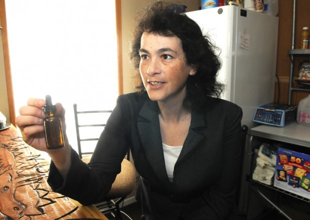 Sheri Levit with a bottle of liquid tincture of cannabis. One of the center's goals is to teach people about the healing benefits of cannabis without smoking it because, she says, smoke in any form is dangerous to one's health. (photo by Mark Ylen/Democrat-Herald)